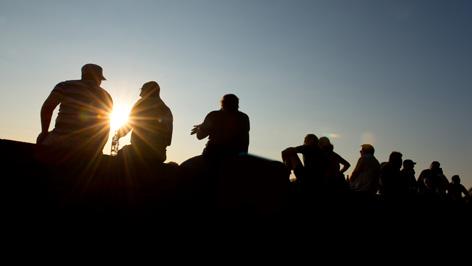 Menschen sitzen auf einer Mauer und betrachten den Sonnenuntergang.