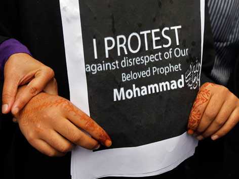 Frau hält Schild mit Text: I protest against disrespect of our beloved prophet Muhammad.