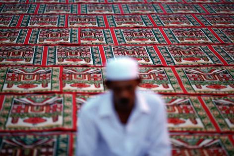 Verschwommene Silhouette eines betenden Muslims auf einem prunkvollen Teppichboden