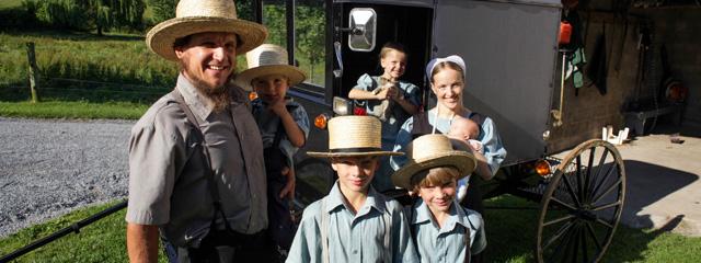 Vater, Mutter und vier Kinder in altmodischer Kleidung vor einem Pferdewagen