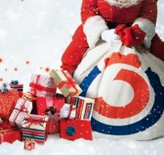Weihnachtsmann sitzt auf einem Sack voll mit Weihnachtsgeschenken