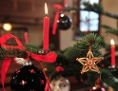 erleuchtete Kerzen am Christbaum umgeben von glänzenden Kugeln