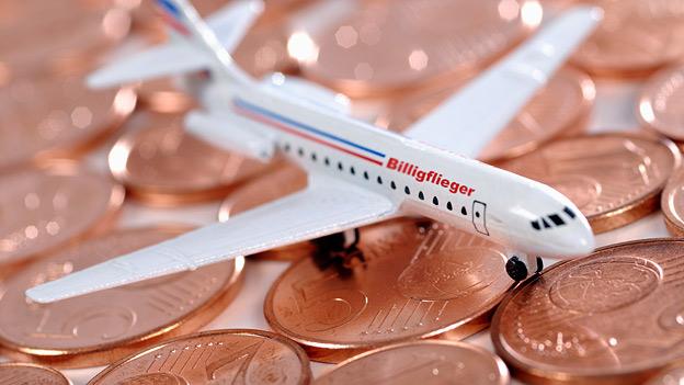 Spielzeugflugzeug steht auf Cent-Münzen