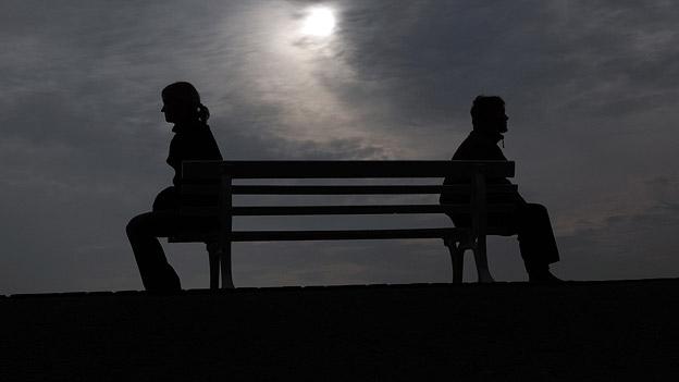 Ein Paar sitzt getrennt auf einer Bank.