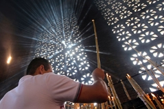 Ein Gottesdienstbesucher zündet nach der Messe eine Kerze an