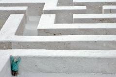 Ein Mädchen versucht in einem Labyrinth eine schneebedeckte Wand zu erklettern