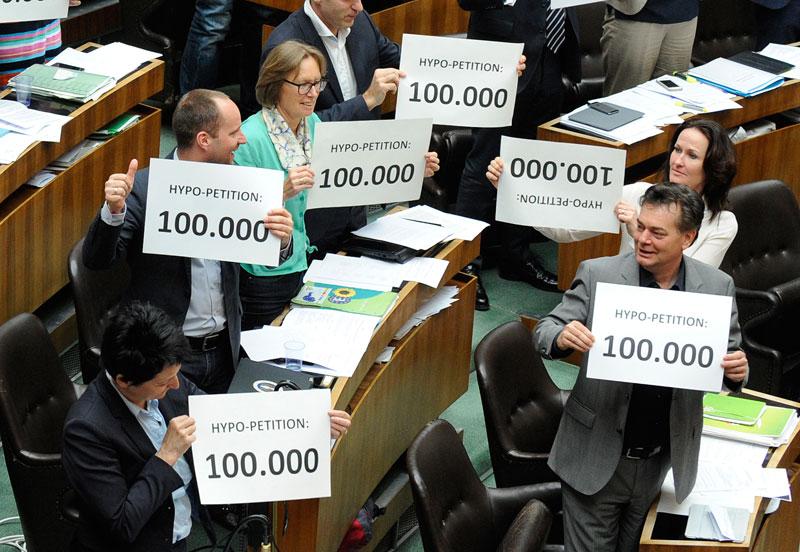 Grüne Abgeordnete mit Taferln zur Hypo-Petition.