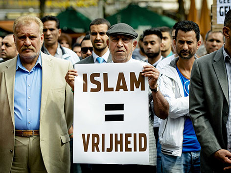 Muslimische Männer demonstrieren gegen ISIS mit Plakaten