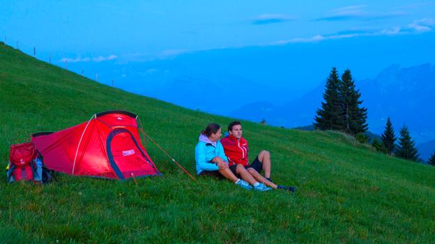 Ein Paar sitzt vor einem Campingzelt
