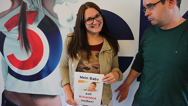 Frau hält Foto mit Baby und Mann schaut entgeistert