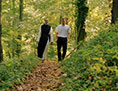 Ein Ordensmann mit einem Pilger beim Wandern im Wald