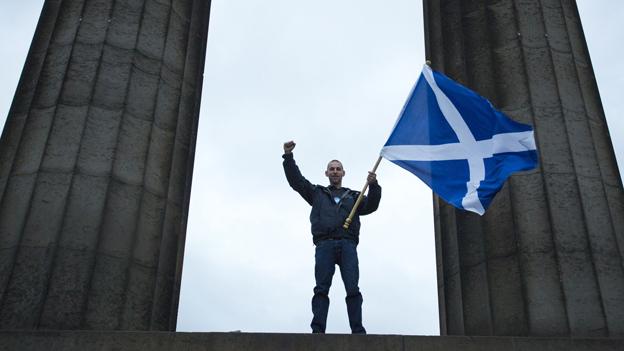Ein Mann schwingt die schottische Flagge auf Scottish National Monument in Calton Hil