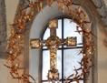 silbernes Kreuz, das von einer goldenen Dornenkrone umgeben ist
