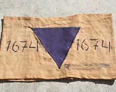 Eine Armbinde aus einem Konzentrationslager mit  einer Nummer und einem violetten Dreieck - zur Kennzeichnung von Zeugen Jehovas.