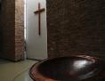 Kreuz im Kirchenraum vor einem dunkelbraunen Taufbecken