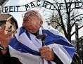 Ein Holocaust-Überlebender spricht vor dem Eingang zum KZ Auschwitz