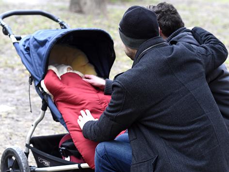 Zwei Männer beugen sich über einen Kinderwagen mit Baby darin