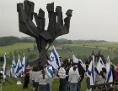 Menschen mit israelischen Flaggen unter einem überdimensionalen siebenarmigen Leuchter, dem jüdischen Mahnmal in Mauthausen