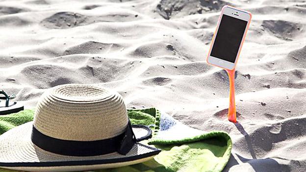 Strohhut im Sand mit Handy