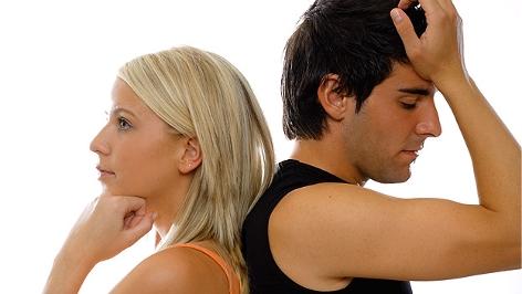 Ein Mann und eine Frau lehnen mit dem Rücken aneinander und wirken nachdenklich