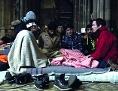 """Filmstill """"Last Shelter"""": Flüchtlinge sitzen mit Caritas-Geschäftsführer Klaus Schwertner auf Matratzen in der Wiener Votivkirche"""