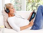 Eine Frau mit Kopfhörern und Tablet auf einem Sofa