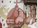 Ein Gemälde auf einer Hauswand mit den religiösen Symbolen Taube, Kreuz, Halbmond