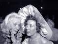 Zwei Frauen tuschlen in einem Theater