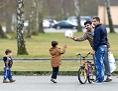 Flüchtlinge, zwei Männer und zwei kleine Kinder mit Fußball und Fahrrädern