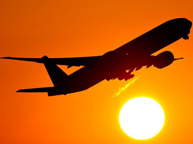 Ein Flugzeug startet in den Sonnenuntergang.