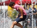 Straßenszene im Sommer: Jugendlicher springt mit Kleidung durch Wasserfontänen