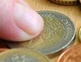 Eine Frau zählt mehrere Euro-Münzen.