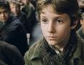 """Ausschnitt aus Film """"Oliver Twist"""": der Proponent steht mit leerer Schüssel vor einer Schar weiterer sitzender Kinder"""