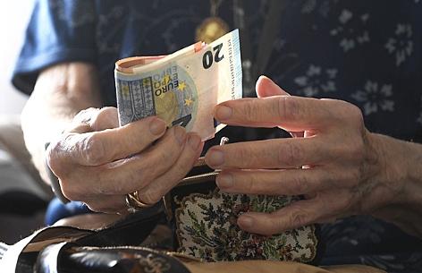 Eine Pensionistin mit Euroscheinen in der Hand