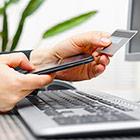 Person hält in der einen Hand ein Smartphone, in der anderen eine Kreditkarte und sitzt vor einem Computer