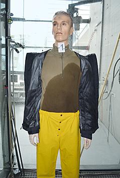 ein Dummy mit nasser Unterwäsche und Funktionsjacke im Regenturm