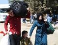 Flüchtlinge in Syrien: Vater, Mutter, Kind mit Koffern und großen Säcken