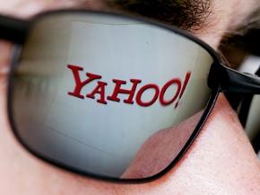 In der Brille eines Mannes spiegelt sich das Logo der Internetseite von Yahoo