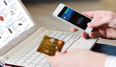 Ein Mann nutzt Smartphone und Kreditkarte um online einzukaufen