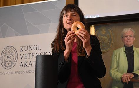Sara Snogerup Linse, die Vorsitzende der Chemiejury, erklärt die preisgekrönte Arbeit anhand eines Brezels