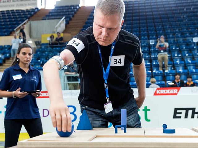 Geschicklichkeitsparcours mit angetriebenen Armprothesen: ein Mann greift nach einer blauen Kugel