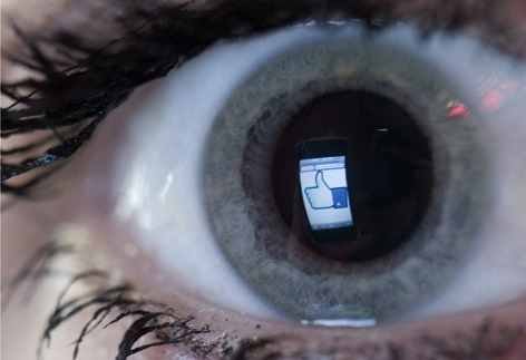 Auge in dem sich ein Facebook Logo spiegelt