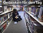 Eine Frau sitzt in einem Gang zwischen Bücherregalen am Boden und liest
