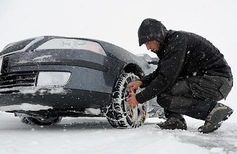 Ein Autofahrer montiert Schneeketten