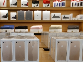 iPhone Schachteln auf dem Tisch eines Apples Stores in Dubai, im Hintergrund Regale mit Apple-Zubehör