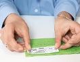 Eine Postbeamtin klebt einen ausgedruckten Portoaufkleber auf einen Brief
