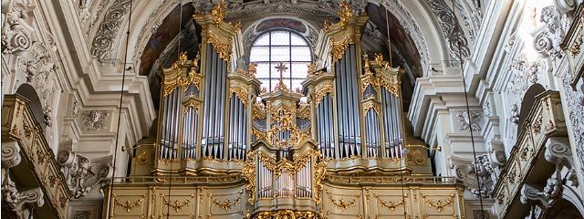 prächtig barocke Orgel in Gold, umgeben von weißem Marmor