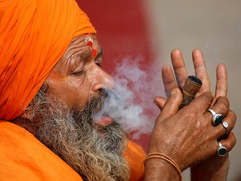 Ein Sadhu - heiliger Mann in Nepal beim Cannabisrauchen zum Fest Shivaratri