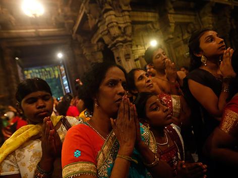 Betende Gläubige Fraeun und junge Männer in einem Hindu-Tempel