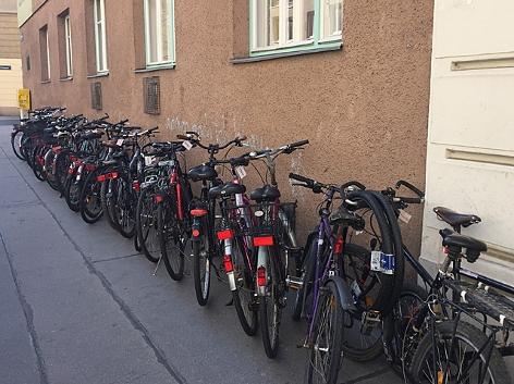Geparkte Fahrräder am Gehsteig vor Werkstatt